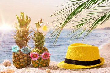 Funny pineapples with hat on sand beach at resort