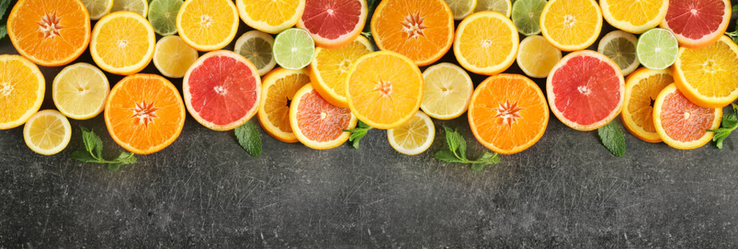 Flat lay composition with ripe citrus fruits on dark background