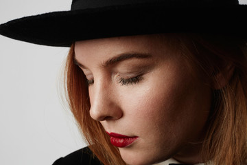 Close up fashion portrait of gorgeous woman in stylish clothes and black hat posing on white background