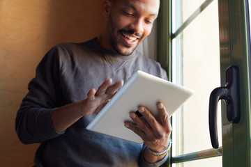 Smiling African black man using tablet at home living room