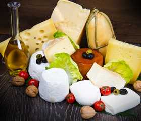 mixed fresh cheese on wooden board