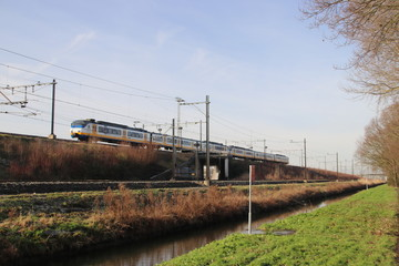 white, blue and yellow local commuter train on track at Zwijndrecht the Netherlands