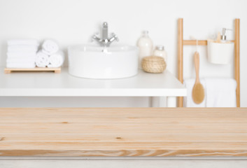 Wooden table top over blurred bathroom interior as the background