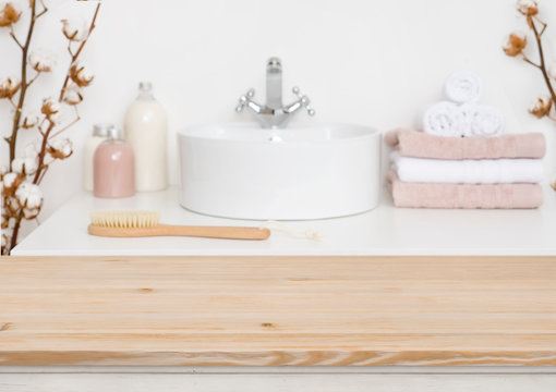 Wooden table top and blur bathroom interior on the background