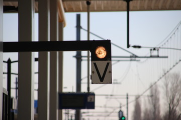 White light with sign V on a railway platform, when lit the train can depart safely