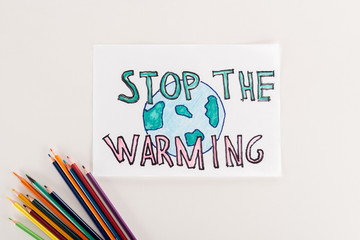 """card with earth symbol and """"stop warming"""" inscription, and multicolored pencils on white background"""