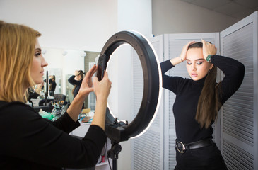 Make up artist taking mobile photo for the model