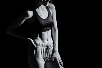 Black and white photo of sporty young woman on dark background