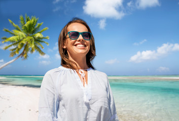 people and leisure concept - happy smiling woman in sunglasses over tropical beach background in french polynesia