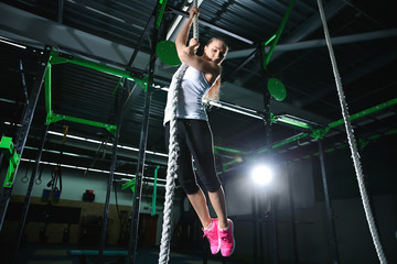 Young sporty woman climbing up the rope in gym