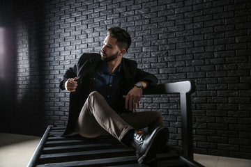 Fashionable young man sitting on bench against dark brick wall