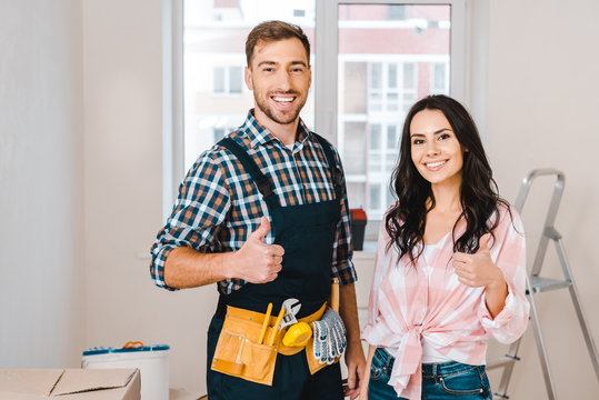 attractive woman and handsome handyman showing thumbs up