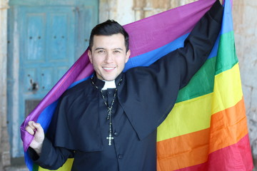 Priest holding the rainbow flag