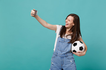 Laughing young woman football fan with soccer ball doing selfie shot on mobile phone isolated on blue turquoise background. People emotions, sport family leisure lifestyle concept. Mock up copy space.