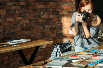 Artist blogger. Drawing and blogging. Woman painter taking photos of artworks. Copy space on brick wall.