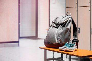 Sports shoes, sport backpack and sport water bottle in gym locker room.