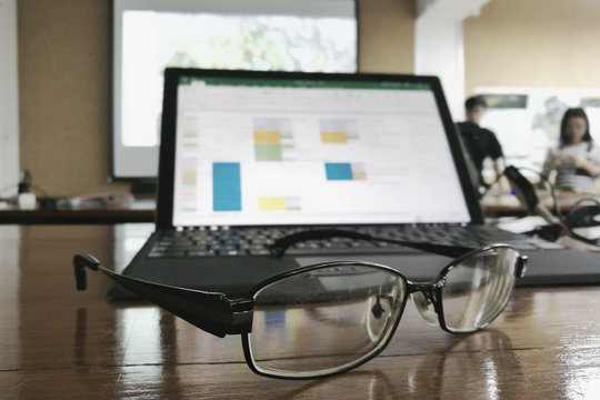 Tired and worn out in a meeting presentation. Glasses in front of a personal computer notebook. blurred data on monitor and people presenting in the backgrounds.
