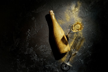 Romantic picture of golden champagne bottle, two wine glasses on black background