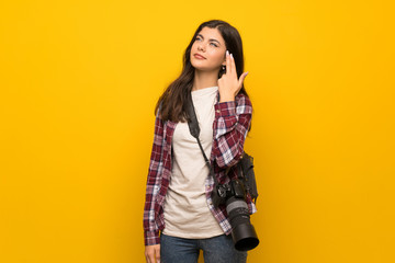 Photographer teenager girl over yellow wall with problems making suicide gesture