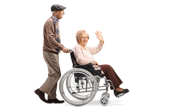 Full length profile shot of a senior man pushing a senior woman in a wheelchair waving isolated on white background