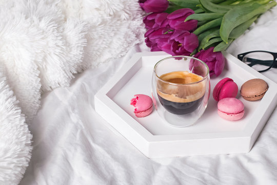A cup of coffee, macarons and tulips on the white bedsheets.