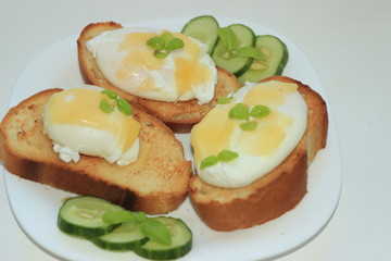 Poached eggs on toasted baguette slices.with a cucumber on a white plate