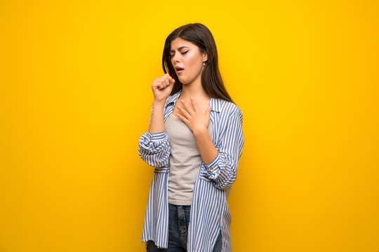 Teenager girl over yellow wall is suffering with cough and feeling bad