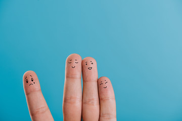 cropped view of happy fingers with one sad isolated on blue