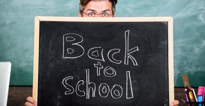 Are you ready study. Teacher or school principal welcomes inscription back to school. Teacher peeking out blackboard. Educator hiding behind blackboard. Buy school supplies. Prepare for school year