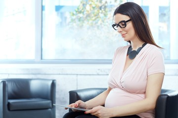 Happy pregnant woman working in modern office