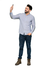 Full-length shot of Elegant man with shirt making a selfie on isolated white background