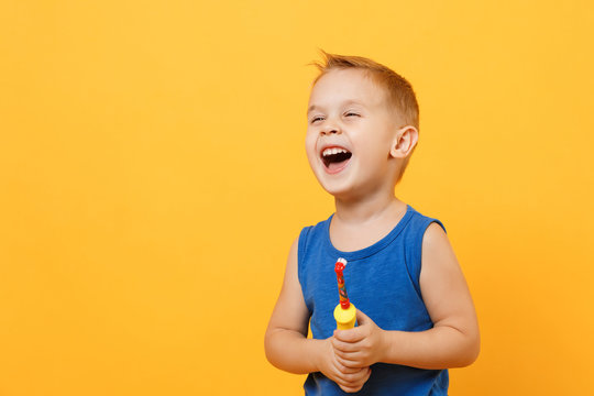 Kid boy 3-4 years old in blue shirt brush his teeth with toothbrush isolated on bright yellow orange wall background, children studio portrait. People, childhood lifestyle concept. Mock up copy space.