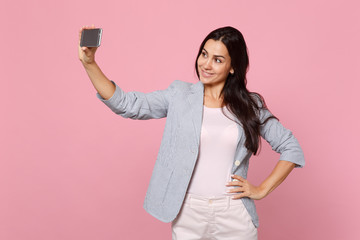 Portrait of stunning pretty young woman in striped jacket doing selfie shot on mobile phone isolated on pink pastel background in studio. People sincere emotions lifestyle concept. Mock up copy space.