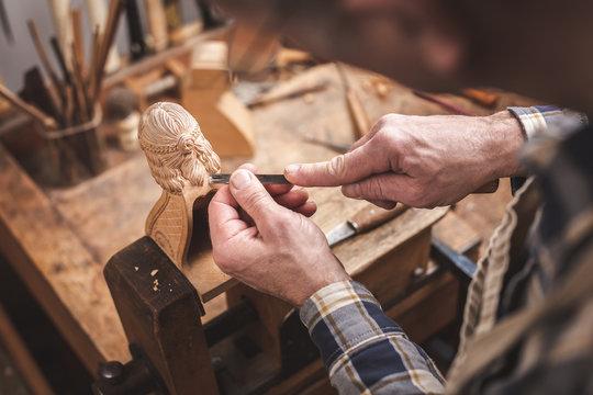 Holzbildhauer beim Schnitzen einer Figur