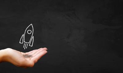 Chalkboard & Hand Showing Rocket Ship