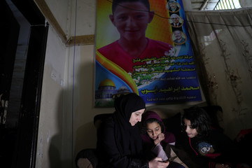 Mother and sisters of Palestinian teenager Mohammad Ayoub look at his picture on a mobile phone at their house in Gaza