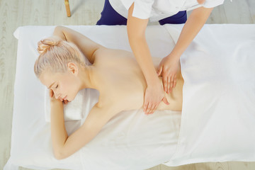 Woman massaging shoulders of client on table