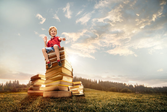 Little boy sitting on the tower made of big books. Childhood dreams, reading and education concept. Wondering world. abstract collage