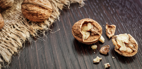 Walnuts on a dark wooden table with rustic background