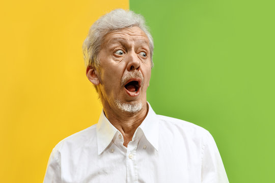 Wow. The senior male portrait on color studio backgroud. emotional surprised bearded man standing with open mouth. Human emotions, facial expression concept. Trendy colors