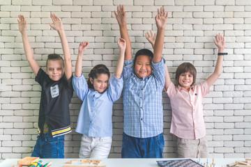 Group of little children raising hands