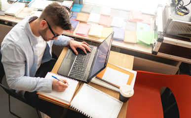 Young man in library on laptop