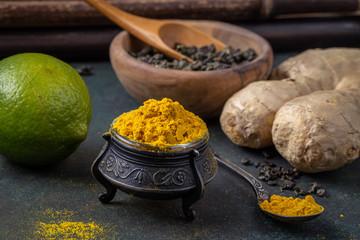 Ingredients for turmeric based healthy tea cooking on dark, closeup