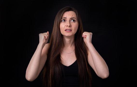 Portrait of a sad brunette woman on a dark background. Misunderstanding, negative emotions.