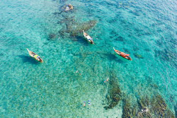View from above, stunning aerial view of some long-tails boats and tourists who do snorkeling in a beautiful, transparent and turquoise sea, Phi Phi Island, Thailand.