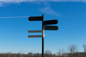 Pole with five blank signposts to fill in text and in a landscape
