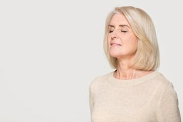 Calm mature woman inhaling taking deep breath of fresh air Wall mural