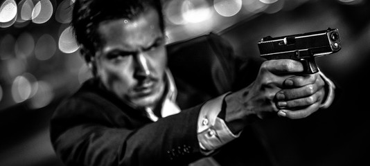 Film Noir style of a male shooting with a handgun in a suit