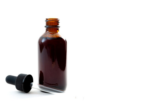 Homeopathic remedy and liquid tincture medicines concept with close up on a brown medicine glass bottles with the dropper out isolated on white background with copy space