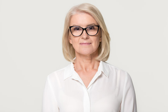 Older businesswoman in glasses looking at camera isolated on background